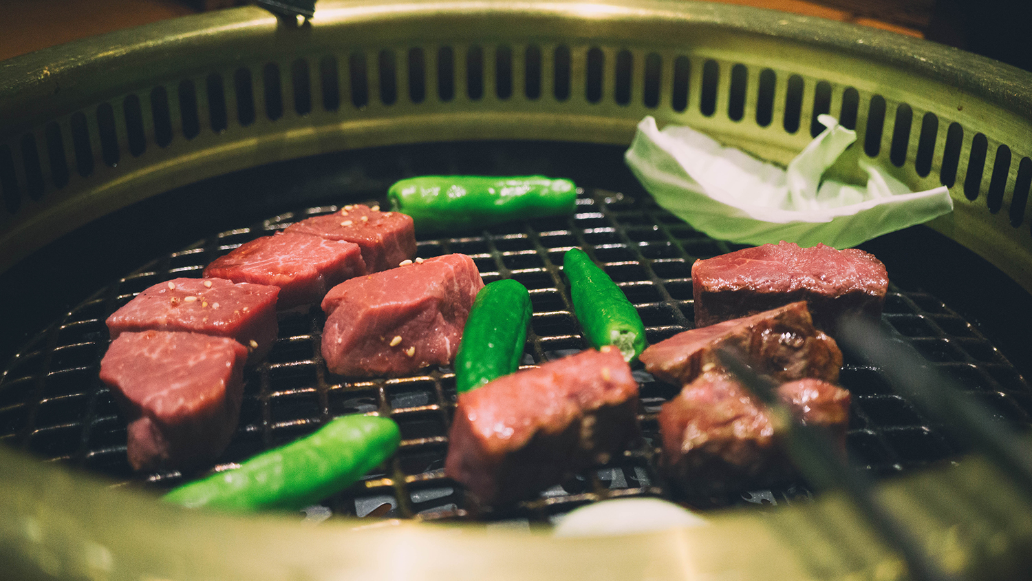 Grilling veggies and meat together.